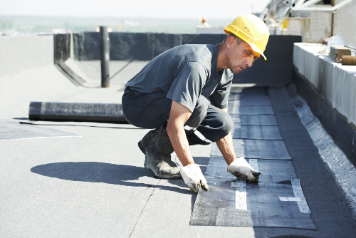 man in yellow hard hat working on flat roof