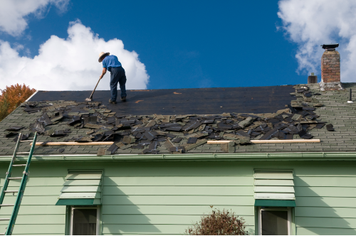 worker on roof sweeping broken shingles